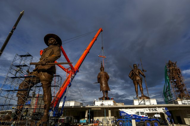 Labourers work on giant bronze statue of former King Taksin (L) at Ratchapakdi Park in Hua Hin, Prachuap Khiri Khan province, Thailand, August 4, 2015. (Photo by Athit Perawongmetha/Reuters)