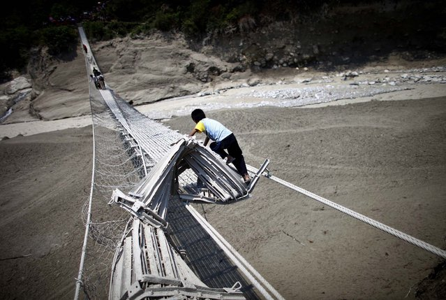Villagers try to cross the Seti river through a damaged suspension bridge about 125 miles west of Katmandu, Nepal
