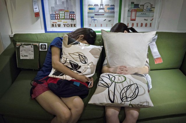 Chinese shoppers clutch pillows as they sleep on a sofa in the showroom of the IKEA store on July 6, 2014 in Beijing, China. Of the world's ten biggest Ikea stores, 8 of them are in China to cater to the country's growing middle class. The stores are designed with extra room displays given the tendency for customers to make a visit an all-day affair. Store management does not discourage shoppers from sleeping on Ikea furniture, even marking them with signs inviting customers to try them out. (Photo by Kevin Frayer/Getty Images)