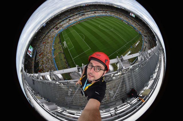 Fisheye picture showing AFP Photographer Francois-Xavier Marit standing point on the catwalk of the roof of Belo Horizonte stadium during the semi-final football match between Brazil and Germany at The Mineirao Stadium in Belo Horizonte during the 2014 FIFA World Cup on July 8, 2014. (Photo by Francois Xavier Marit/AFP Photo)