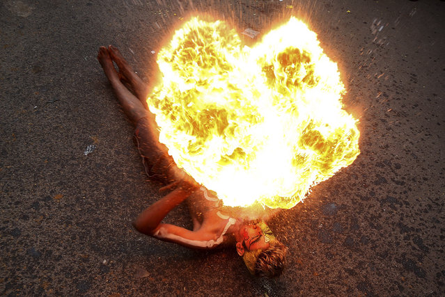 """An Indian artist performs with fire during a procession as part of """"Bonalu"""" festival in Hyderabad, India, Monday, Aug.10, 2015. Bonalu is a month long Hindu folk festival of India's Telangana region dedicated to Kali, the Hindu goddess of destruction. (Photo by Mahesh Kumar A./AP Photo)"""