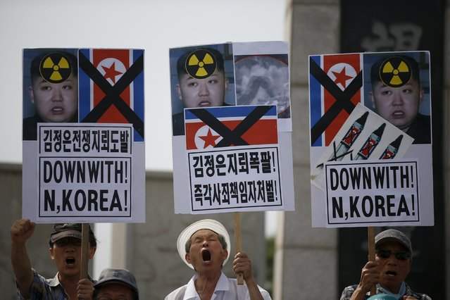 Men from an anti-North Korea and conservative civic group chant slogans during an anti-North Korean rally near the demilitarized zone separating the two Koreas in Paju, South Korea, August 11, 2015. South Korea's military on Monday threatened retaliation against North Korea after accusing the North of planting land mines inside the Demilitarised Zone border that wounded two soldiers last week, in what it called a cowardly act of provocation. (Photo by Kim Hong-Ji/Reuters)
