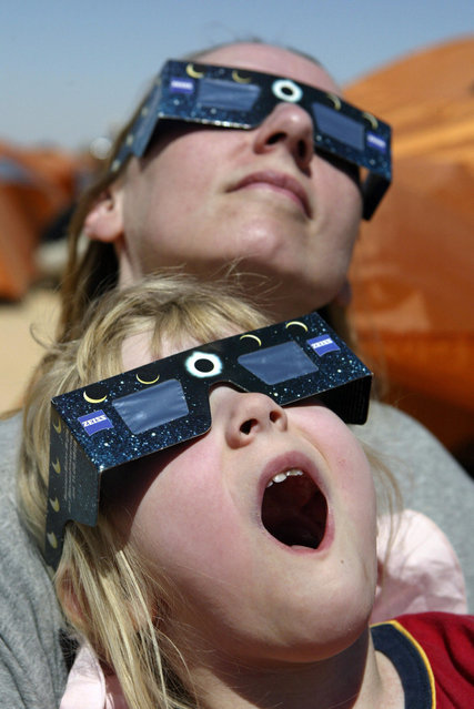 An Australian girl and her mother watch the solar eclipse in the desert tourist camp in Galo, 1300 km south of the Libyan capital of Tripoli, March 29, 2006. Thousands of astronomers and thrill-seekers gazed heavenward, prayers were said by the faithful and schools shut for the day as the three-hour celestial ballet raced across half the world. (Photo by Khaled Desouki/AFP Photo)