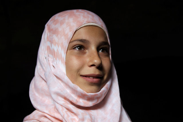 Internally displaced girl Shahed Shahine, 13, attends a class inside a cave in the rebel-controlled village of Tramla, in Idlib province, Syria March 27, 2016. (Photo by Khalil Ashawi/Reuters)