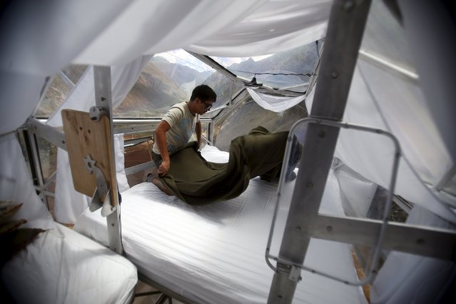 A guide cleans a sleeping pod at the Skylodge Adventure Suites in the Sacred Valley in Cuzco, Peru, August 14, 2015. (Photo by Pilar Olivares/Reuters)