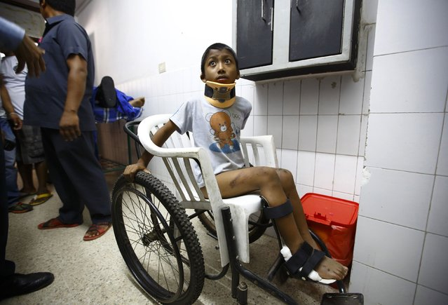 A boy waits to get his X-ray done at a hospital in Kathmandu after being rescued from a landslide in northeast Nepal August 2, 2014. A massive landslide triggered by heavy rains in northeast Nepal on Saturday has killed at least eight people, injured 40 and buried dozens of homes, officials said. The landslide created a mud dam blocking the Sunkoshi River near Jure in the Sindhupalchowk district, about 60 kms (37 miles) northeast of Kathmandu. (Photo by Navesh Chitrakar/Reuters)