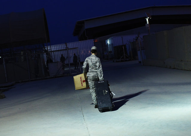 U.S. Air Force Major Stacie Shafran carries her luggage to a loading paddock while waiting for her departure from Iraq at the former U.S. Sather Air Base near Baghdad, Iraq, December 14, 2011. (Photo by Shannon Stapleton/Reuters)