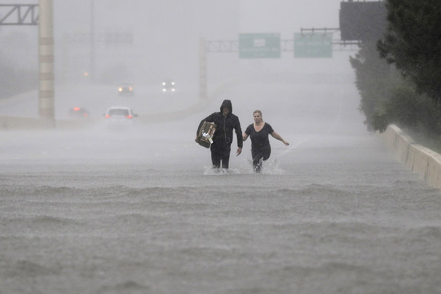 Two people walk down a flooded section of Interstate 610 in floodwaters from Tropical Storm Harvey on Sunday, August 27, 2017, in Houston, Texas. (Photo by David J. Phillip/AP Photo)