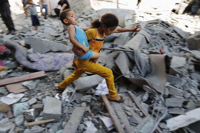 A Palestinian girl carries a child across rubble from a building that police said was destroyed by an Israeli air strike, in the Burij refugee camp in the central Gaza Strip August 1, 2014. (Photo by Finbarr O'Reilly/Reuters)