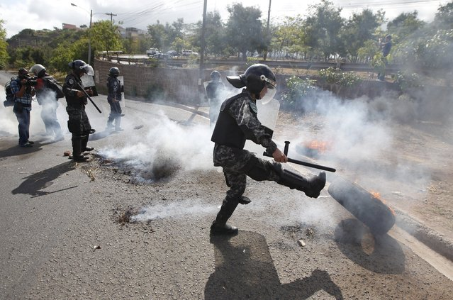 A policeman kicks a burning tyre used by demonstrators to block a road as part of a protest to demand the resignation of Honduran President Juan Orlando Hernandez in Tegucigalpa, Honduras, August 26, 2015. The protesters are calling for Hernandez's resignation over a $200 million corruption scandal at the Honduran Institute of Social Security (IHSS). (Photo by Jorge Cabrera/Reuters)