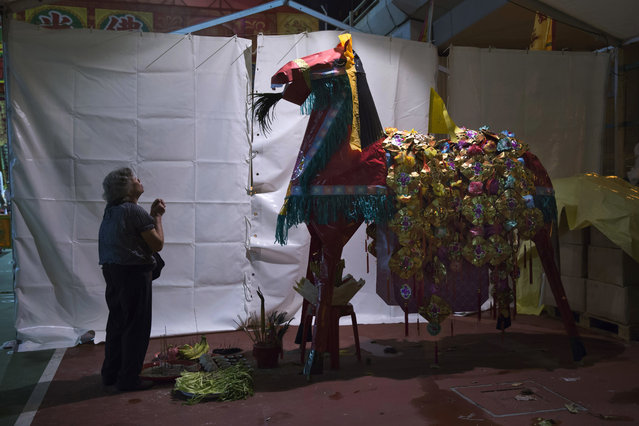 """In this August 31, 2017, photo, a worshiper prays in front of a paper horse effigy during the """"Hungry Ghost Festival"""" in Hong Kong. (Photo by Kin Cheung/AP Photo)"""