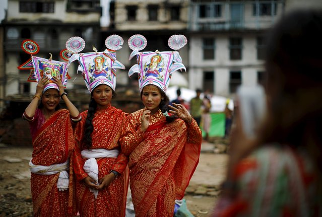 Girls depicting holy cows pose for pictures for a friend before they take part in a parade to mark the Gaijatra Festival, also known as the festival of cows, in Kathmandu, Nepal August 30, 2015. Hindus in Kathmandu celebrate the festival to ask for salvation and peace for their departed loved ones. Cows are regarded as holy animals in Nepal that help departed souls reach heaven. (Photo by Navesh Chitrakar/Reuters)