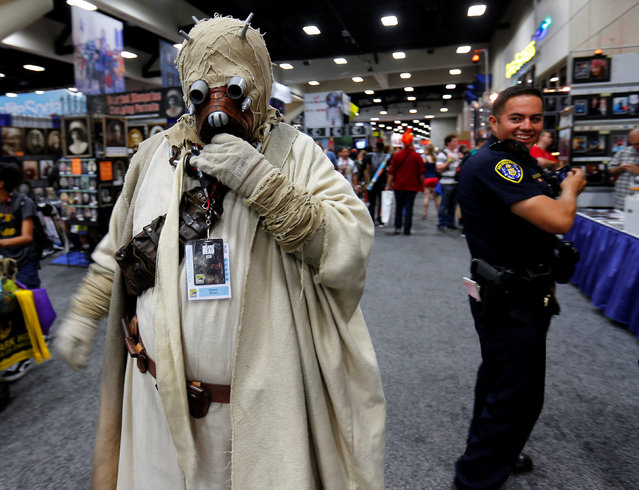 A San Diego police officer takes a second look at an attendee's Star Wars Tusken Raider costume while patrolling the convention floor during opening day of Comic-Con International in San Diego, California, United States July 21, 2016. (Photo by Mike Blake/Reuters)