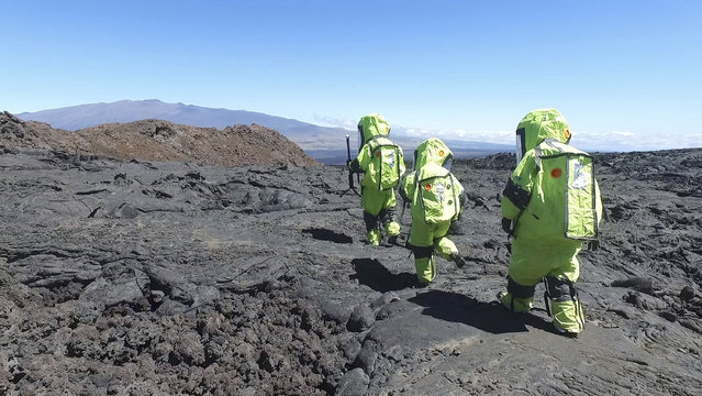 In this 2017 photo released by the University of Hawaii crew members of Mission V, walk across lava next to the university's facility Hawaii Space Exploration Analog and Simulation (HI-SEAS) at the Mauna Loa volcano, Big Island, Hawaii. After eight months of living in isolation on a remote Hawaii volcano, six NASA-backed space psychology research subjects will emerge from their Mars-like habitat on Sunday, September 17, 2017. The participants are in a study designed to better understand the psychological impacts of a long-term manned mission to space on astronauts. NASA hopes to send humans to Mars by the 2030s. (Photo by University of Hawaii via AP Photo)