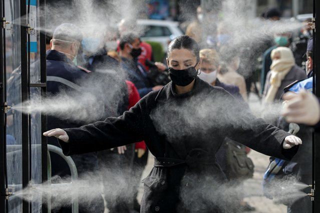 Albanian people are being disinfected before entering a market, as Albanian authorities take measures to stop the spread of the coronavirus disease (COVID-19) in Tirana, Albania on April 6, 2020. (Photo by Florion Goga/Reuters)