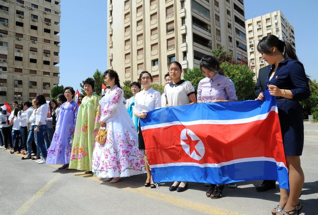 Young women hold a North-Korean flag during a ceremony to name a park in Damascus after Kim Il-sung, the late founder and supreme leader of the Democratic People's Republic of Korea (DPRK), on August 31, 2015 in the Kafar Susseh neighbourhood at the occasion of the 70th anniversary of Korea's liberation from the 1910-45 Japanese colonial rule. (Photo by AFP Photo/Stringer)