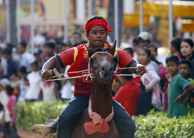 A boy rides on his horse for racing as part of the festival of Pchum Ben, or Ancestors' Day at Vihear Sour pagoda in Kandal province, northeast of Phnom Penh, Cambodia, Wednesday, September 20, 2017. Residents of the village on Wednesday held the annual water buffalo race to mark the end of the traditional 15-day religious festival, which commemorates the spirits of the dead, widely known in the country as Festival for the Dead. (Photo by Heng Sinith/AP Photo)