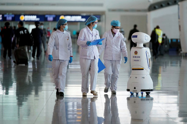 Medical workers walk by a police robot at the Wuhan Tianhe International Airport after travel restrictions to leave Wuhan, the capital of Hubei province and China's epicentre of the novel coronavirus disease (COVID-19) outbreak, were lifted, April 8, 2020. (Photo by Aly Song/Reuters)