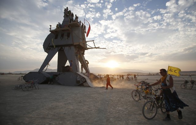 "Participants interact with the Alien Siege Machine during the Burning Man 2014 ""Caravansary"" arts and music festival in the Black Rock Desert of Nevada, August 28, 2014. People from all over the world have gathered at the sold out festival to spend a week in the remote desert cut off from much of the outside world to experience art, music and the unique community that develops. (Photo by Jim Urquhart/Reuters)"