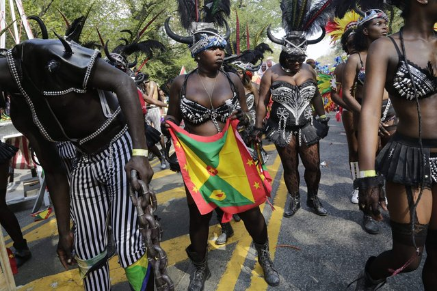Dancers perform for spectators during the West Indian Day Parade, Monday, September 1, 2014 in the Brooklyn borough of New York. (Photo by Mark Lennihan/AP Photo)