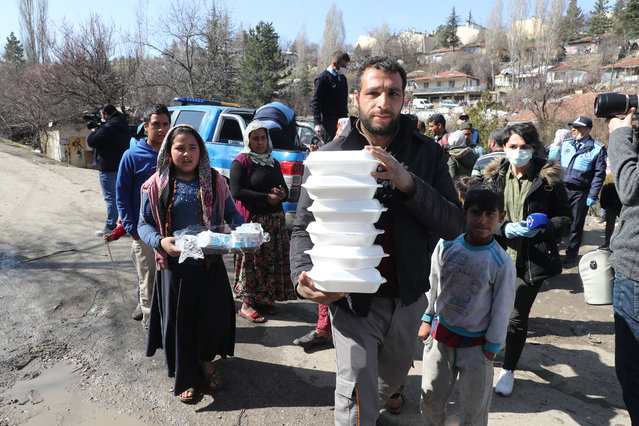 Metropolitan Municipality workers hand out food to a community in Ankara on March 23, 2020, as part of measures taken to prevent the spread of the Covid-19 disease caused by the novel coronavirus. Turkey has announced a raft of measures to limit the spread of the virus, including the closure of schools and universities, and shutting mosques to mass gatherings. (Photo by Adem Altan/AFP Photo)