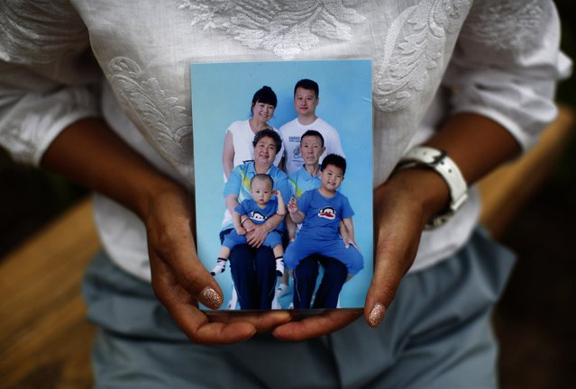 Cheng Liping, whose husband Ju was onboard Malaysia Airlines Flight MH370 which disappeared on March 8, 2014 shows a family photo featuring her missing husband (top, R) at a park near her house where she and her husband used to visit, during an interview with Reuters in Beijing July 24, 2014. (Photo by Kim Kyung-Hoon/Reuters)
