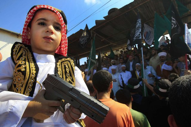 A boy holds a toy gun during a protest about a film ridiculing Islam's Prophet Muhammad in the Palestinian refugee camp of Ain el-Hilweh near Sidon, Lebanon, September 14, 2012. (Photo by Mohammed Zaatari/Associated Press)