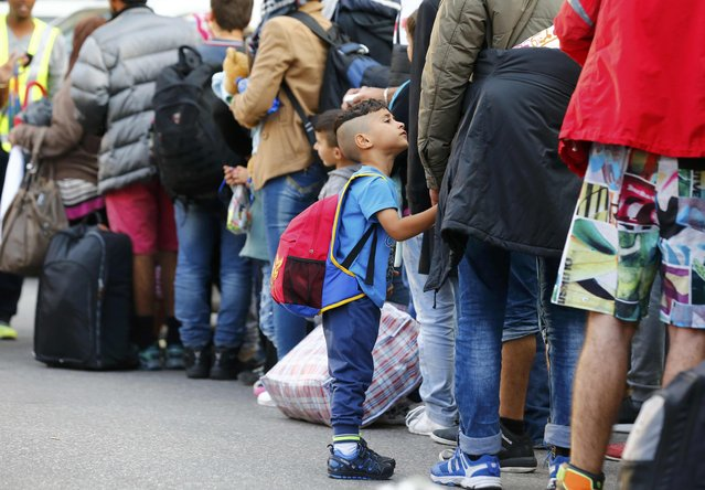 Migrants wait in a queue after arriving by train to the main railway station in Munich, Germany September 5, 2015. (Photo by Michael Dalder/Reuters)