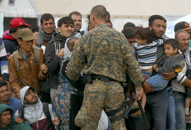 A police officer tries to maintain order while migrants wait for trains at a temporary camp near Gevgelija, Macedonia, September 7, 2015. (Photo by Stoyan Nenov/Reuters)