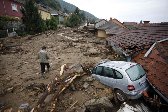 A man passes by a damaged vehicle on a street covered with mud due to heavy floods in Tekija village September 17, 2014. (Photo by Djordje Kojadinovic/Reuters)
