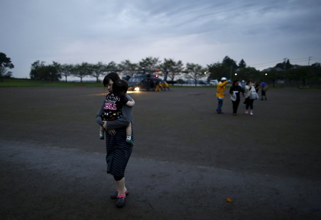 Evacuees are escorted by rescue workers after being rescued by a helicopter from an area flooded by the Kinugawa river, caused by typhoon Etau, upon their arrival at Ishige Sports Park acting as an evacuation center in Joso, Ibaraki prefecture, Japan, September 10, 2015. (Photo by Issei Kato/Reuters)