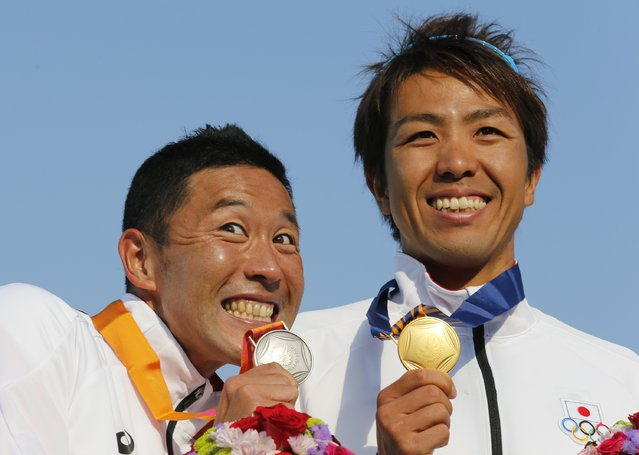 Gold medalist Yuichi Hosoda (R) of Japan and compatriot silver medalist Hirokatsu Tayama pose with their medals on the podium at an award ceremony for the men's triathlon competition at Songdo Central Park during the 17th Asian Games in Incheon September 25, 2014. (Photo by Kim Kyung-Hoon/Reuters)