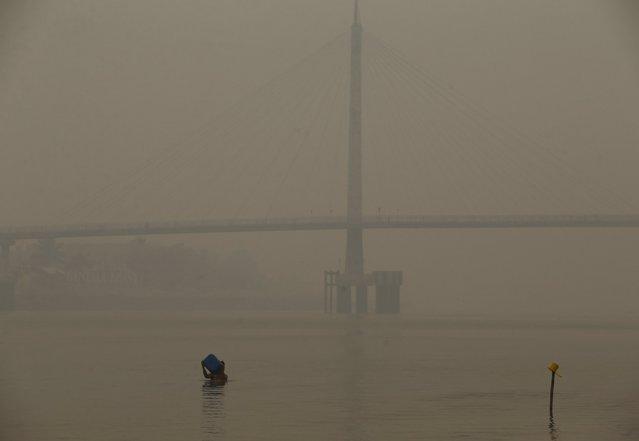 A resident takes a bath as the haze shrouded Batanghari River in Jambi, on Indonesia's Sumatra island, September 15, 2015. (Photo by Reuters/Beawiharta)