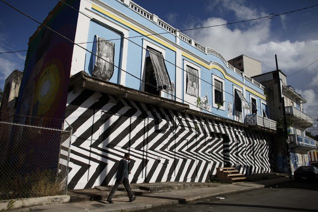 In this September 22, 2014 photo, a man walks in front of a building with street art murals painted in the Santurce neighborhood in San Juan, Puerto Rico. Some people trace Santurce's comeback to the government-led restoration of La Placita, a plaza that features an outdoor produce market surrounded by bars and restaurants, some considered to be among the best in Puerto Rico. (Photo by Ricardo Arduengo/AP Photo)