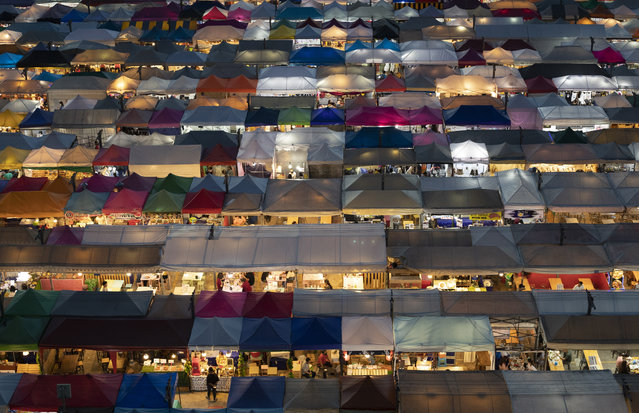 Tents of food stalls and other vendors are illuminated at Rot Fai Market in Bangkok, Thailand, Friday, June 19, 2020. Daily life in the capital resumes to normal as the government continues to ease restrictions related to running business and activities that were imposed weeks ago to combat the spread of COVID-19. Thailand reported no local transmissions of the coronavirus in the past 3 weeks. (Photo by Sakchai Lalit/AP Photo)