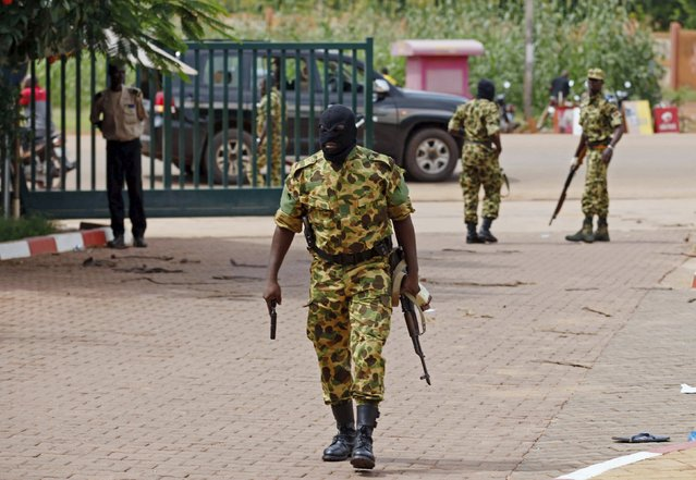 Presidential guard members arrive at the Laico hotel in Ouagadougou, Burkina Faso, September 20, 2015. Pro-coup demonstrators in Burkina Faso on Sunday invaded the hotel due to host talks aimed at hammering out the details of a deal to restore a civilian interim government and attacked participants arriving for the meeting, witnesses said. (Photo by Joe Penney/Reuters)