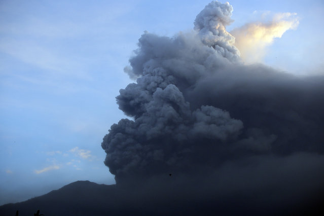 A view of the Mount Agung volcano erupting at sunrise in Karangasem, Bali island, Indonesia, Sunday, November 26, 2017. (Photo by Firdia Lisnawati/AP Photo)