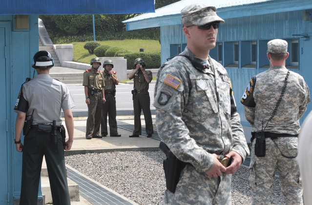 In this July 27, 2014 file photo, North Korean army soldiers watch the south side while a South Korean and United States Army soldiers stand guard at the border villages of Panmunjom in Paju, South Korea. North Korea has threatened on Saturday, August 27, 2016, to aim fire at the lighting equipment used by American and South Korean troops at a truce village inside the Demilitarized Zone that divides the two Korea. (Photo by Ahn Young-joon/AP Photo)