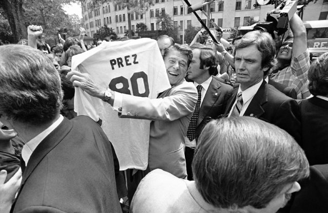 """GOP presidential candidate Ronald Reagan holds up a """"Prez"""" football jersey presented him by someone in the crowd in Baton Rouge, Louisiana, Tuesday, September 23, 1980. Regan made and address on the campus of Louisiana State University. (Photo by Charles Harrity/AP Photo)"""