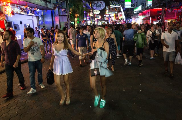 Women walk along the Walking Street where bars and s*x scenes are a commonplace July 31, 2016 in Pattaya, Thailand. (Photo by Tsering Topgyal/AP Photo)