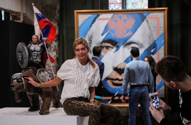 """A woman poses for a picture with a sculpture depicting Russian president Vladimir Putin riding a bear at the """"SUPERPUTIN"""" exhibition at UMAM museum in Moscow, Russia on December 6, 2017. (Photo by Maxim Shemetov/Reuters)"""