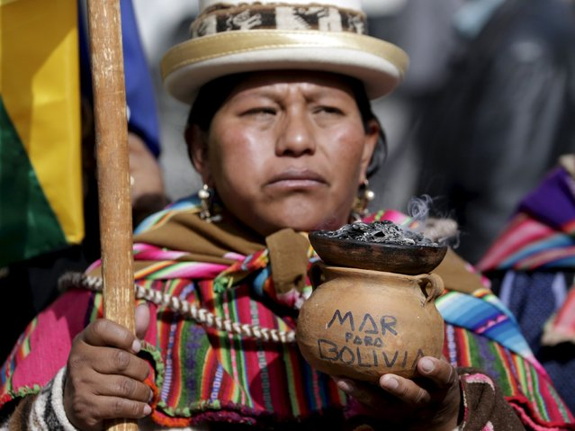 "A witch doctor attends a ceremony at Murillo Square after learning of the statement made by the International Court of Justice (CIJ), in La Paz, September 24, 2015. The words on her ceremonial vessel reads, ""Sea for Bolivia"". (Photo by David Mercado/Reuters)"
