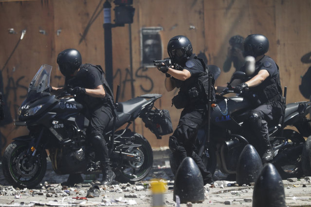 Motorized police fire rubber bullets at protesters during a general strike against a pension reform measure, outside Congress in Buenos Aires, Argentina, Monday, December 18, 2017. Union leaders complain the legislation, which already passed in the Senate, would cut pension and retirement payments as well as aid for some of poor families. (Photo by Victor R. Caivano/AP Photo)