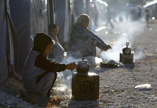 Kurdish refugees from the Syrian town of Kobani prepare tea in a camp in the southeastern town of Suruc, Sanliurfa province on October 20, 2014. The U.S. military said it had air-dropped arms to Syrian rebels fighting Islamic State militants near Kobani on Sunday in what appeared to be the Pentagon's first public acknowledgment it has delivered lethal aid to the rebels. (Photo by Kai Pfaffenbach/Reuters)