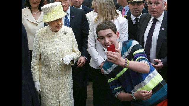 A local youth takes a selfie photograph in front of Queen Elizabeth II during a visit to St George's indoor market on June 24, 2014 in Belfast, Northern Ireland. (Photo by Peter Macdiarmid/AFP Photo)