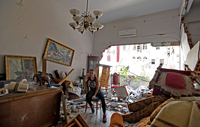 A woman sits amidst the rubble in her damaged house in the Lebanese capital Beirut on August 6, 2020, two days after a massive explosion shook the Lebanese capital. The blast, which appeared to have been caused by a fire igniting 2,750 tonnes of ammonium nitrate left unsecured in a warehouse, was felt as far away as Cyprus, some 150 miles (240 kilometres) to the northwest. The scale of the destruction was such that the Lebanese capital resembled the scene of an earthquake, with thousands of people left homeless and thousands more cramming into overwhelmed hospitals for treatment. (Photo by AFP Photo/Stringer)