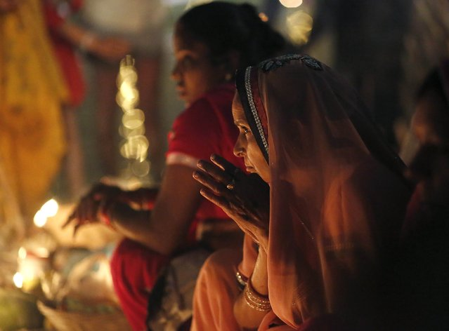 Hindu women worship the Sun god Surya by the waters of the river Yamuna during the Hindu religious festival of Chatt Puja in New Delhi October 30, 2014. (Photo by Anindito Mukherjee/Reuters)