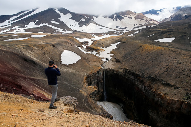 A tourist takes a photograph of a waterfall on the Vulkannaya River in Opasny Canyon at the foot of Mount Mutnovsky in the Southern Kamchatka Regional Nature Park, on Russia's Pacific coast on July 15, 2020. The Southern Kamchatka Regional Park is part of a group of nature parks known as the Volcanoes of Kamchatka Park, which has been on the UNESCO World Heritage List since 1996. (Photo by Yelena Vereshchaka/TASS)