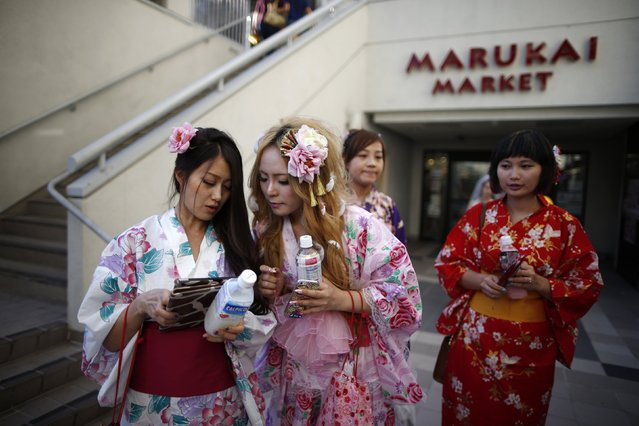 Miyako Cai (2nd L), 26, chats to friends as she walks out of a Japanese supermarket in the Little Tokyo area of Los Angeles, California August 10, 2014. (Photo by Lucy Nicholson/Reuters)