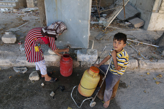 Children fill containers with water in the rebel held al-Maadi district of Aleppo, Syria, August 31, 2016. (Photo by Abdalrhman Ismail/Reuters)